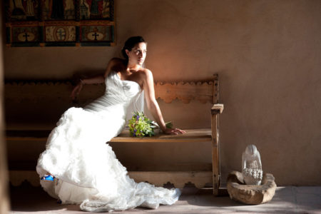 Bride in white dress on Southwestern bench with adobe wall