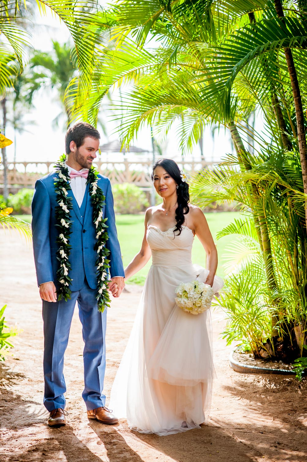 Hawaii wedding couple holding hands in lush greenery
