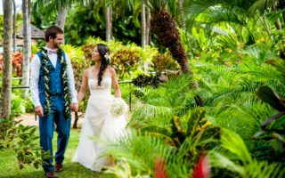 hawaii wedding couple holding hands and walking in lush greenery