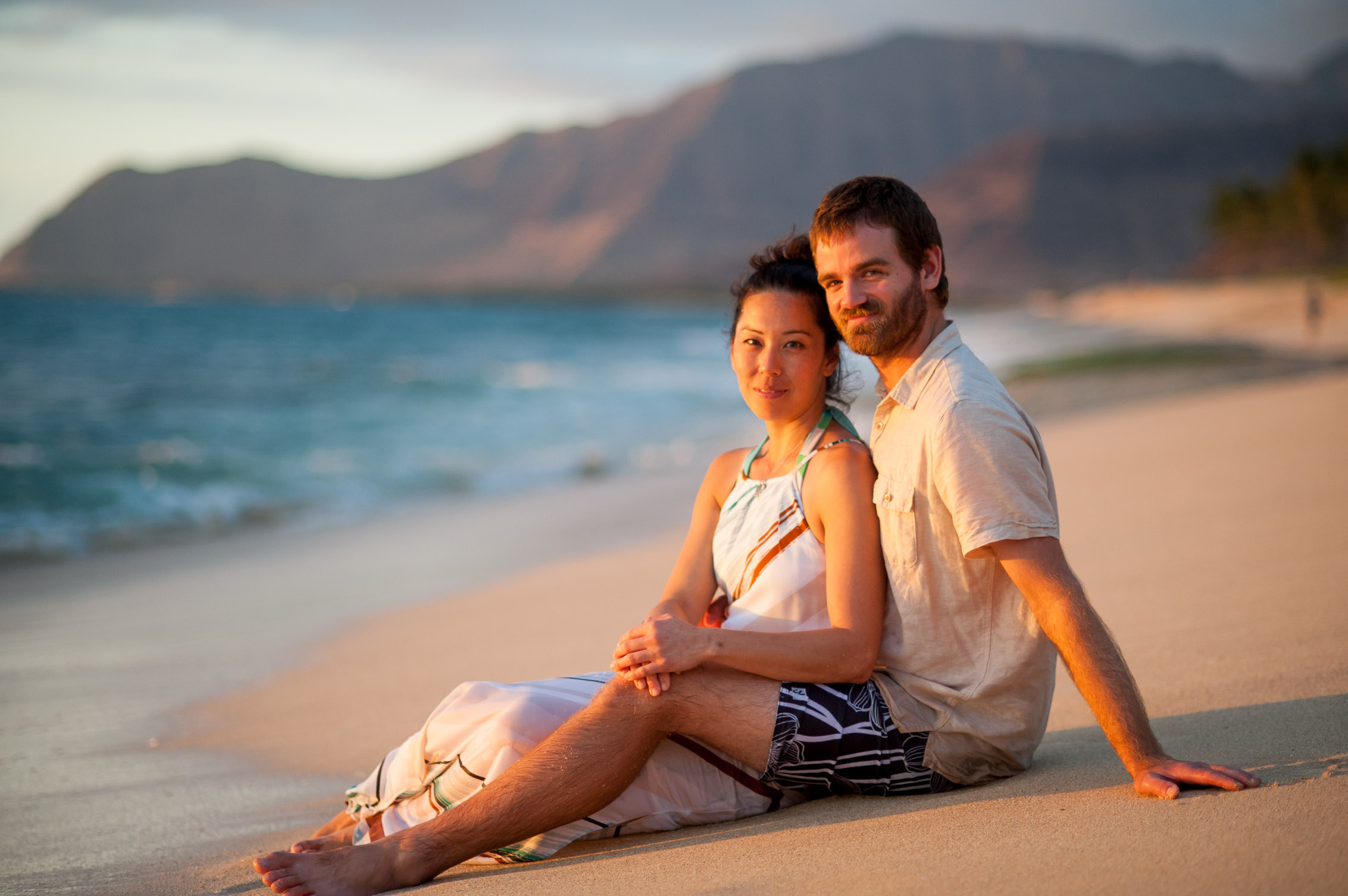 couple embracing on the beach at sunset in hawaii