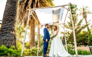 Jewish wedding couple under the chuppah with palm trees