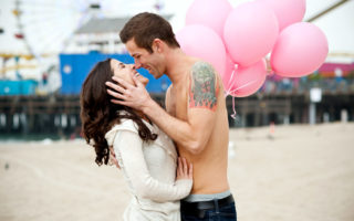 Couple kissing with pink balloons in front of pier