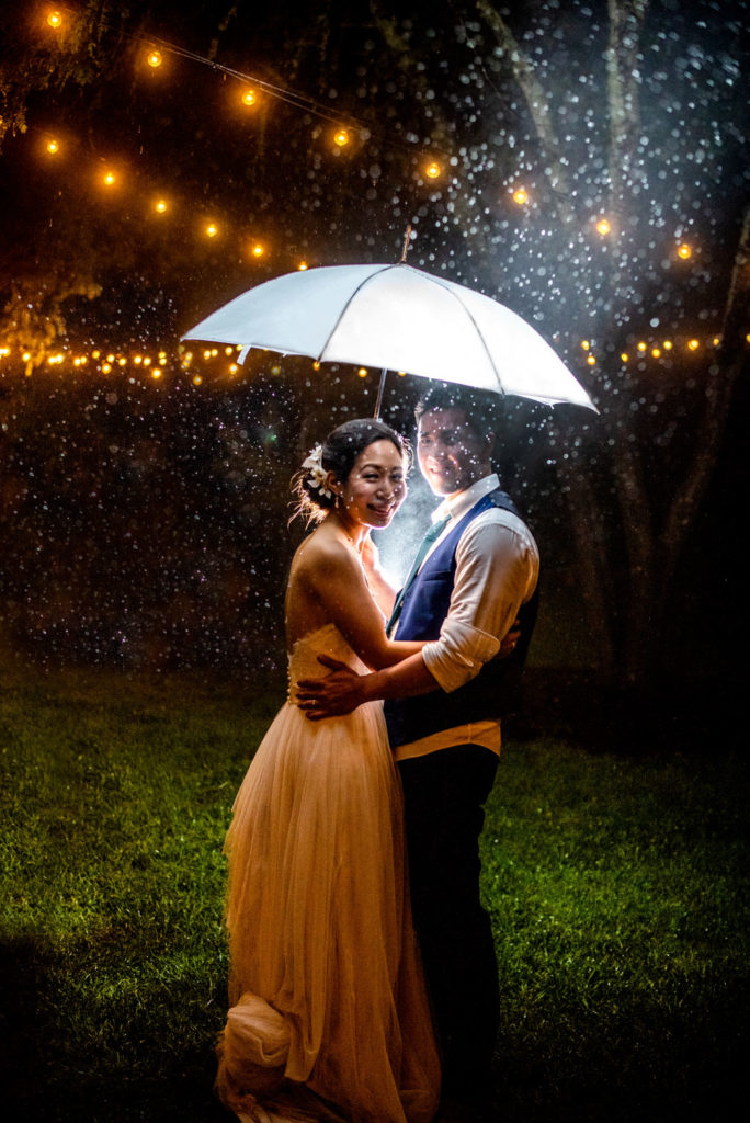 Bride and Groom in the night rain with umbrella and string lights