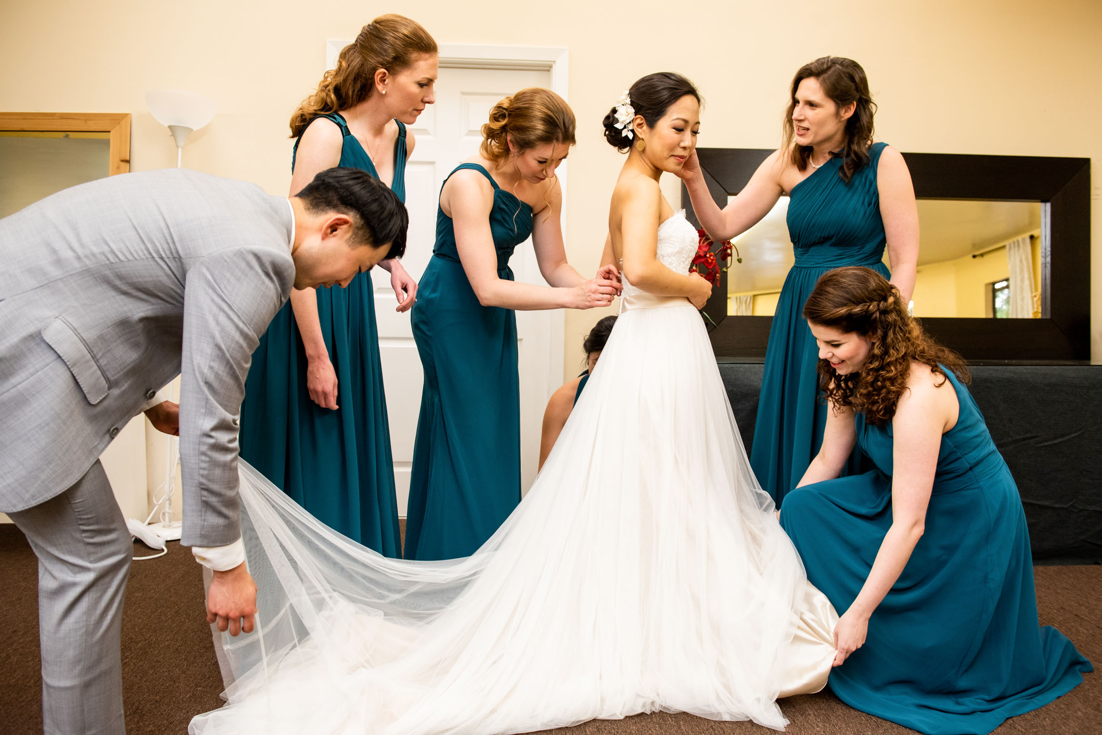 Four bridesmaids and bridesman help the bride get ready
