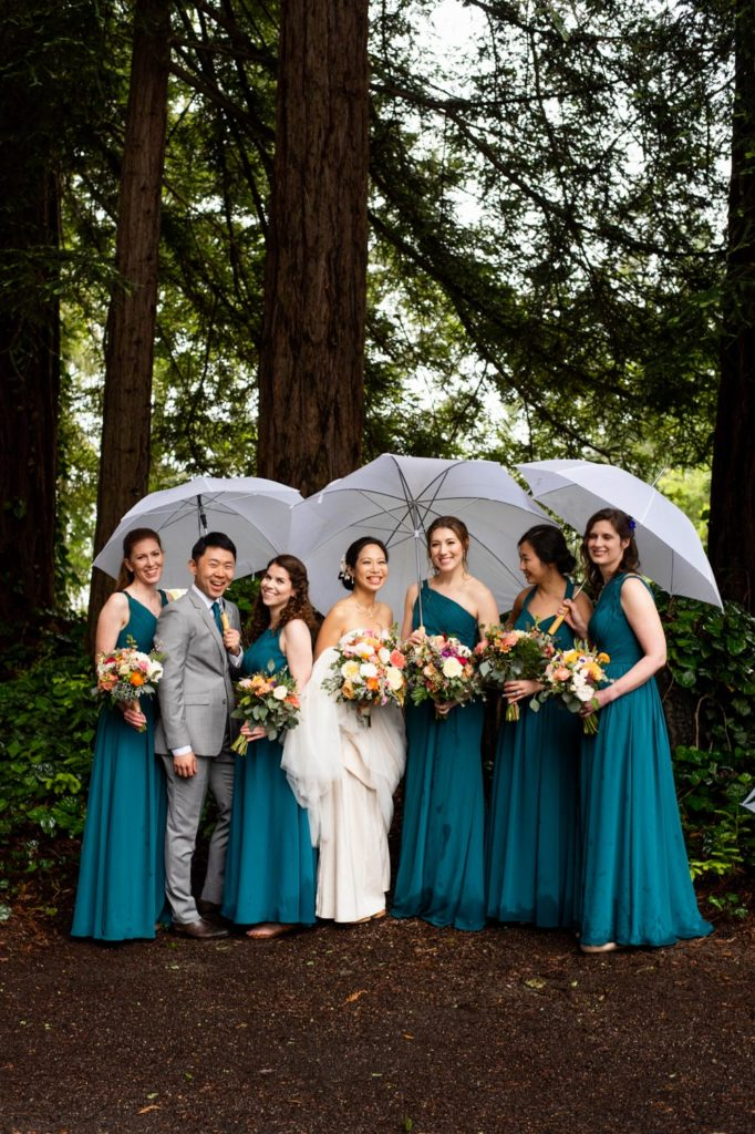 The bride with her bridesmaids and bridesman under white umbrellas