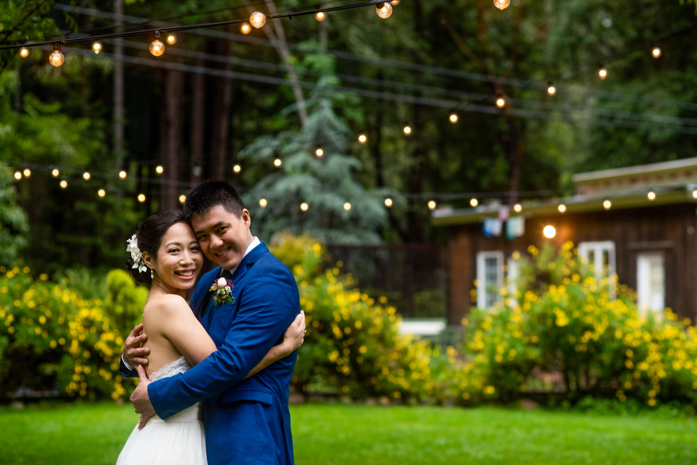 Bride and groom embrace on green lawn with string lights
