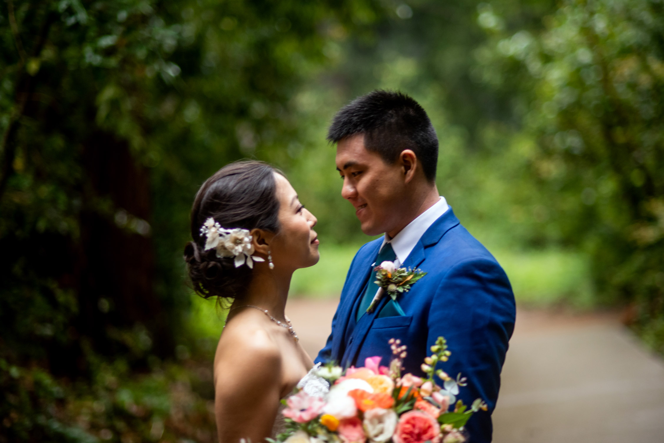 Bride and groom face to face in lush forest with flowers