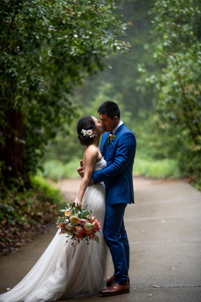 Bride and groom kiss in the fog and light rain