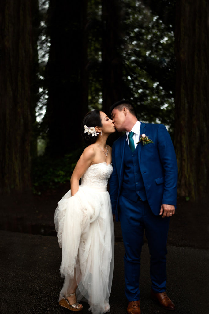 The bride holds her long white dress as she kisses her groom in the redwood forest