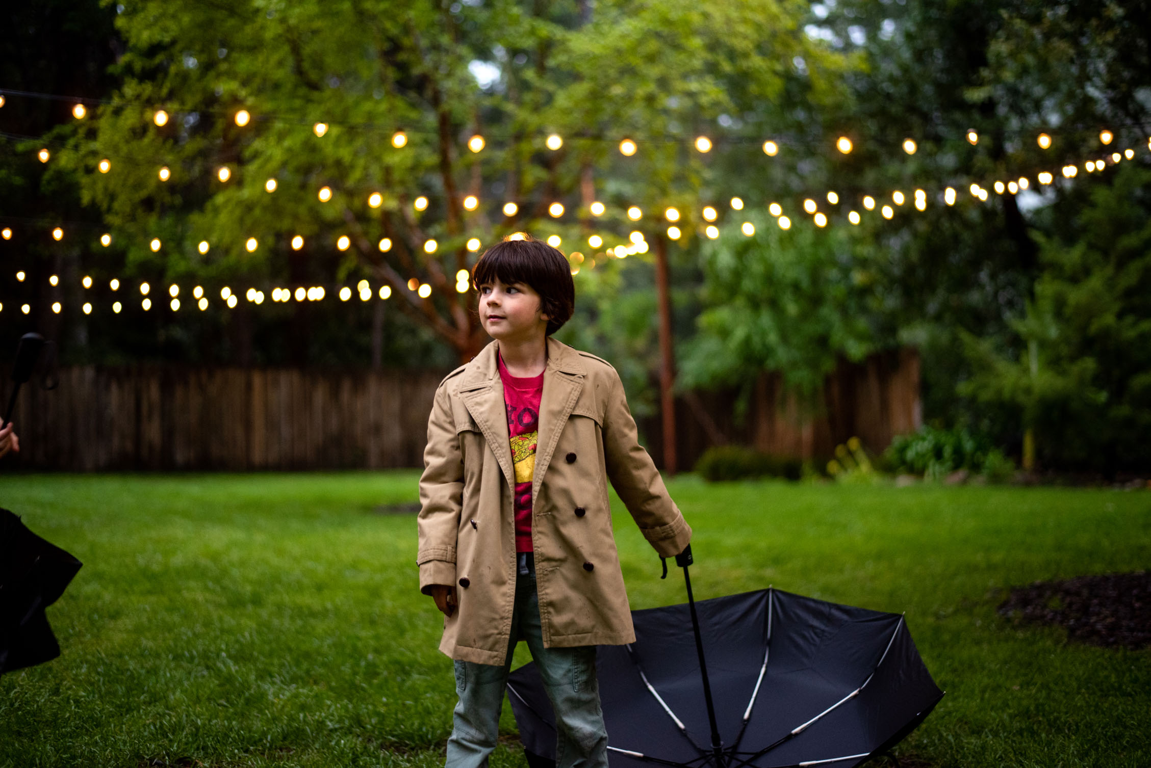 Young boy with umbrella standing under the string lights