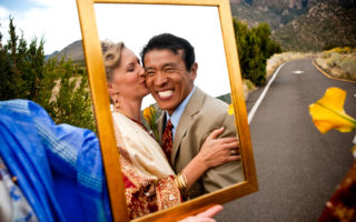 Tibetan groom smiling in mirror reflection on wedding day